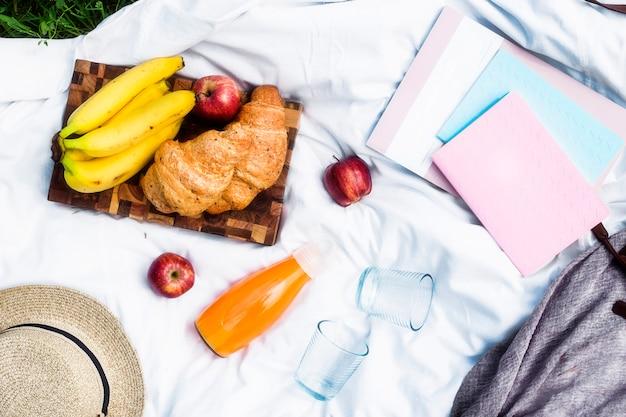 クロワッサンとジュースのある公園でのピクニック