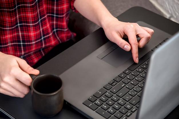 女性の手がノートパソコンのキーを押す