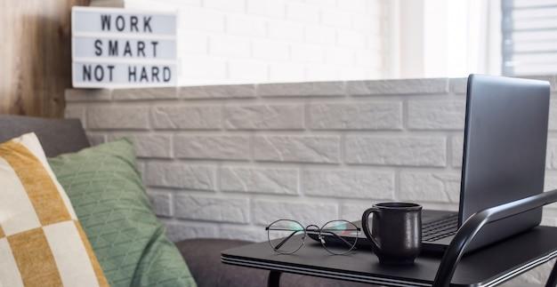 ソファとレンガの壁の近くの黒のスタイリッシュなテーブルでフリーランサーの自宅の職場