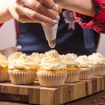 青いエプロンと格子縞の赤いシャツの女性菓子は、カップケーキにクリームを適用します