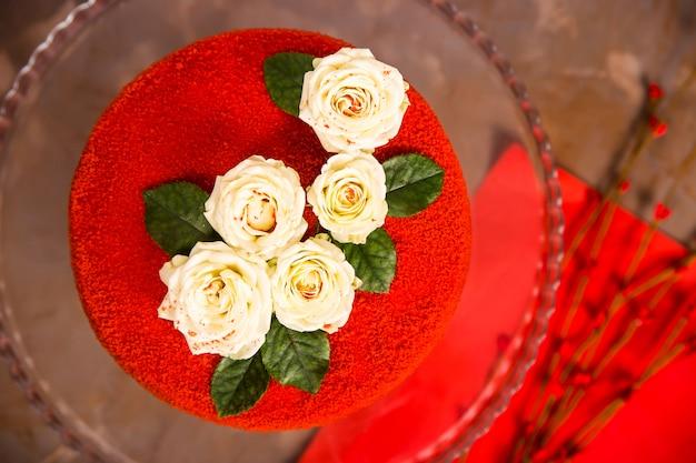 Красный бархатный торт украшен белыми маленькими розочками с зелеными листьями