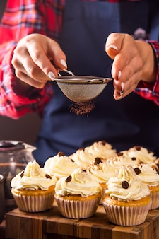 女性の菓子はティラミスココアパウダーでカップケーキを飾る