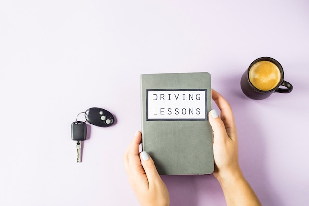 女性の手はレッスンを運転し、交通規則を研究するためのトレーニング本を持っています