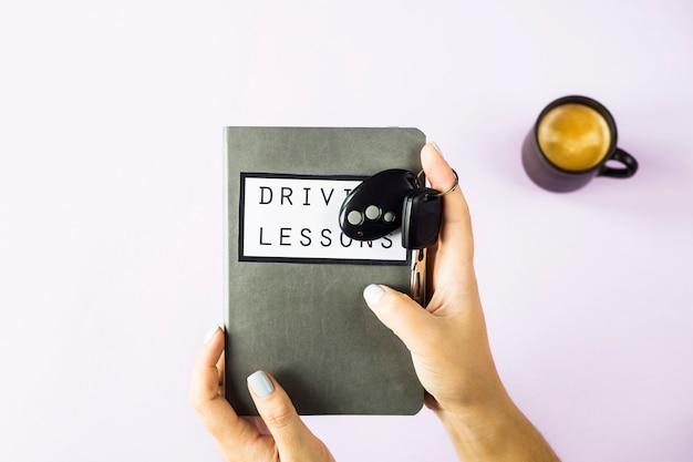 女性の手がレッスンを運転し、交通ルールと車のキーを勉強するためのトレーニング本を持っています