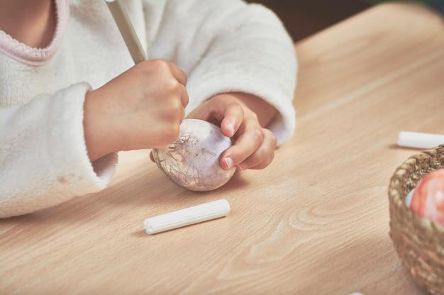 彼らのお母さんの助けを借りてと家庭でのマーカーでイースターエッグを塗る子供たち