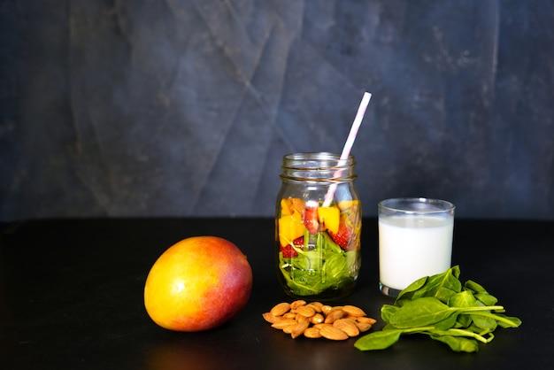 健康的なグリーンリーチビタミンスムージーの成分、赤ちゃんのほうれん草、マンゴー、アーモンドミルク、ストロベリー