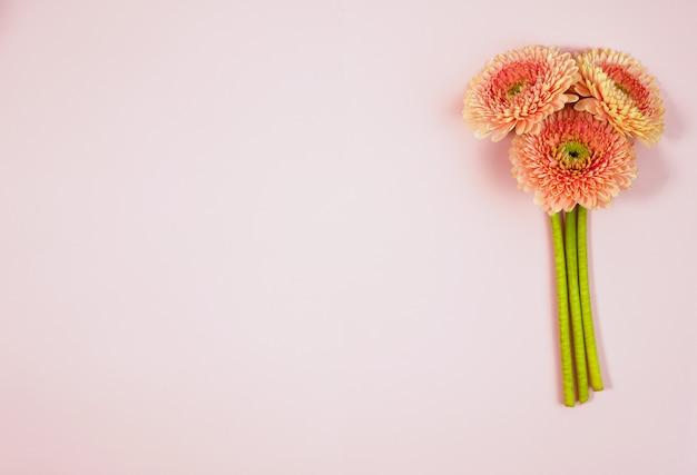 青いパステル調のテーブルトップビューで美しい春のピンクの花。花のボーダー。平干しスタイル。
