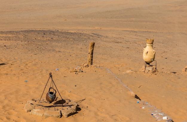 やかんと砂の背景に水差し