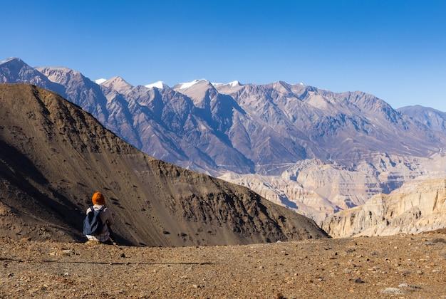 座っていると山々を見てバックパックを持つ少女