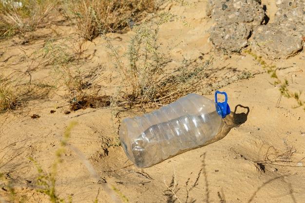Пустая пластиковая бутылка лежит на песке