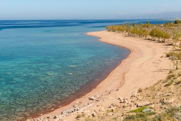 Озеро иссык-куль, кыргызстан, пустой песчаный пляж на южном берегу озера