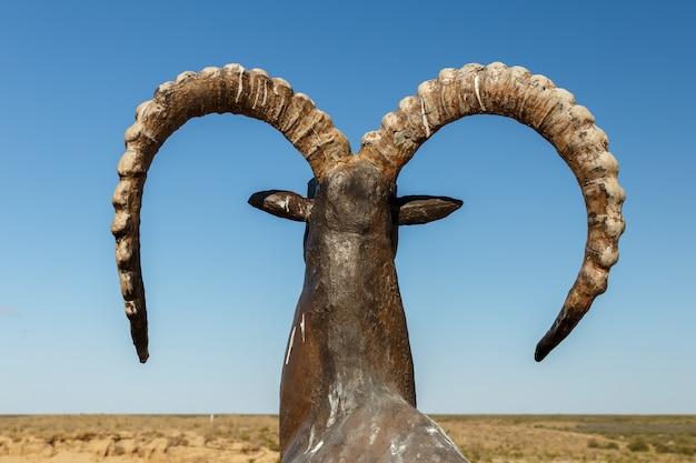 青い空、背面図と角の丸まったヤギの像