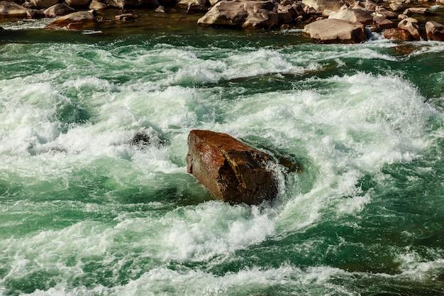 大きな石は山の川の真ん中にあり、川は流れて石を回ります。川の泡の作成