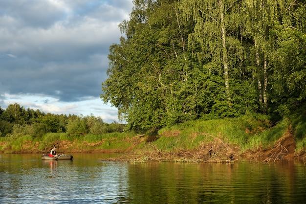 男が川で魚を捕る