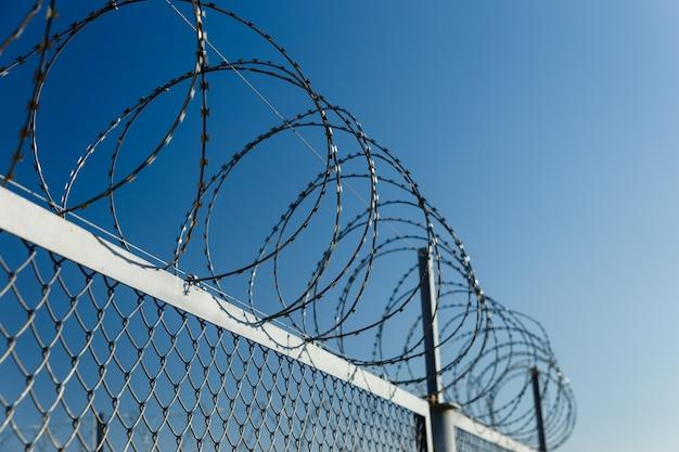 Забор с колючей проволокой, колючей проволокой на заборе.