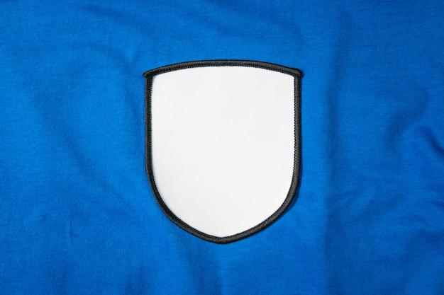 青いスポーツシャツに空白の腕パッチ。あなたのモンタージュや編集のための白いチームのロゴとエンブレム。