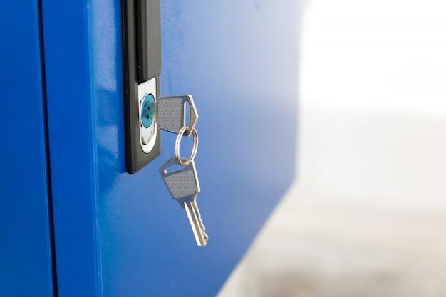Голубой шкафчик и цепочка для ключей в спортзале школы.