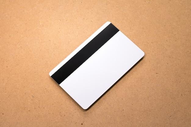 木製の背景に白のカード。あなたのデザインのための空白のクレジットカードのテンプレート。