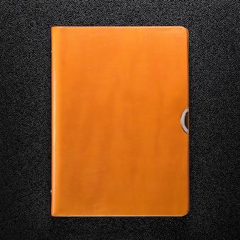 暗い背景にオレンジ色の革の本。ハードカバーの本の正面図。