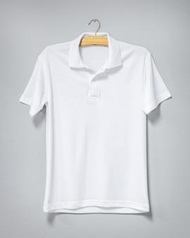 Белая рубашка висит на цементной стене. пустая футболка для печати. передний план.
