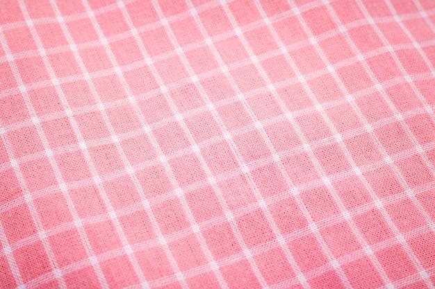 ピンクのテーブルクロスの背景のクローズアップ。ピクニックパターンの生地の詳細。
