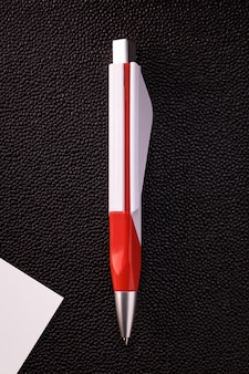 Темная ручка и белая карточка на темном фоне.