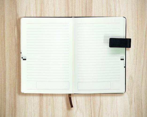 木材の背景に開かれた本の平面図です。ホワイトペーパーの空白のテンプレート。