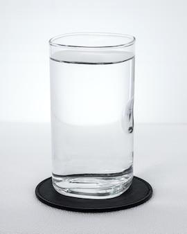 白い背景の上の水のガラスと黒の飲料コースター。