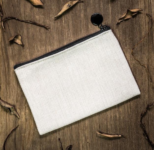 Белая текстильная сумка на деревянных фоне.