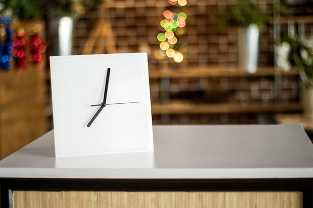 モダンな棚の上の白い時計。ミラーフレームまたは室内の室内装飾。