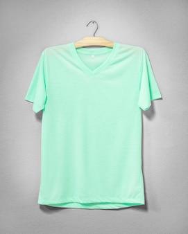 Зеленая рубашка висит на цементной стене.