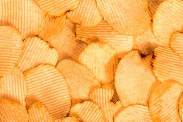 ポテトチップスの背景。ファーストフードのスナックの質感。