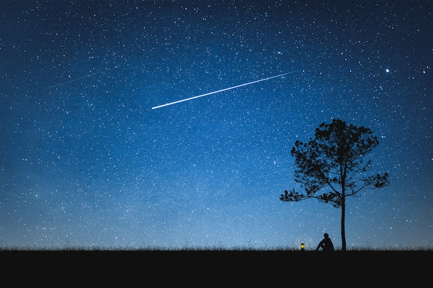 流れ星と山と夜空に座っている男のシルエット。一人でコンセプト。