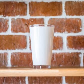 ヴィンテージのレンガ壁の背景に背の高いマグカップ。