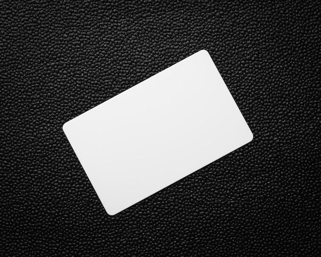 Белая карточка на фоне темной кожи. пустая визитка.