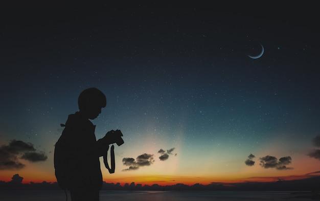 月と夜の空と自然に立っている写真家のシルエット。