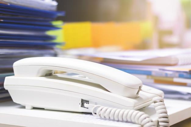 電話と事務机の上の未完成の文書がたくさんのクローズアップ。