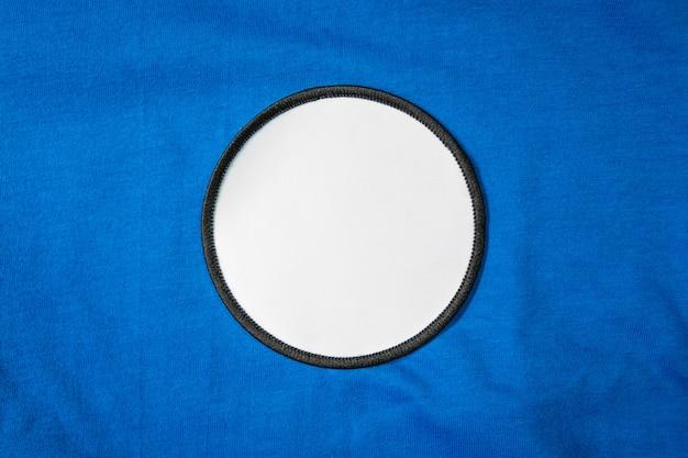 青いスポーツシャツに空白の腕パッチ。ホワイトチームのロゴとエンブレム。