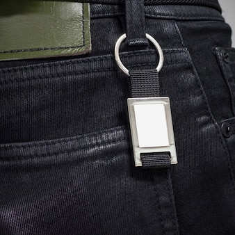 Стальное кольцо для ключей висит на черных джинсах.