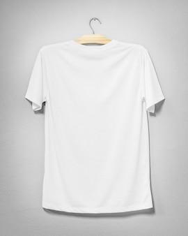 セメントの壁に掛かっている白いシャツ