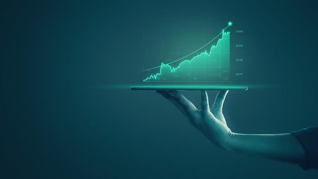 タブレットを保持し、ホログラフィックグラフと株式市場の統計を示すビジネスマンは利益を得る。