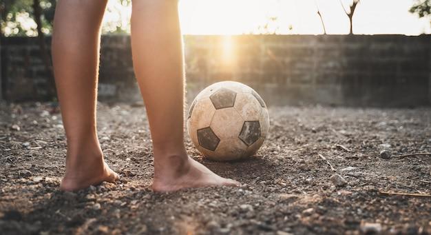 Бедный ребенок играет в старый футбол или футбол на земле со светящимся солнечным светом