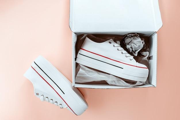 Белые модные белые кроссовки в картонной коробке на кремово-персиковом фоне