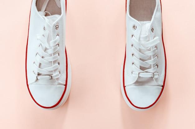 Белые модные белые кроссовки на кремово-персиковом фоне. плоская планировка, вид сверху. место для текста. минималистичный стиль композиции.