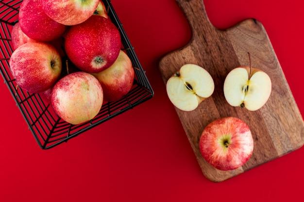 Красные яблоки в металлической черной корзине на темно-красном фоне. вид сверху плоская планировочная композиция.
