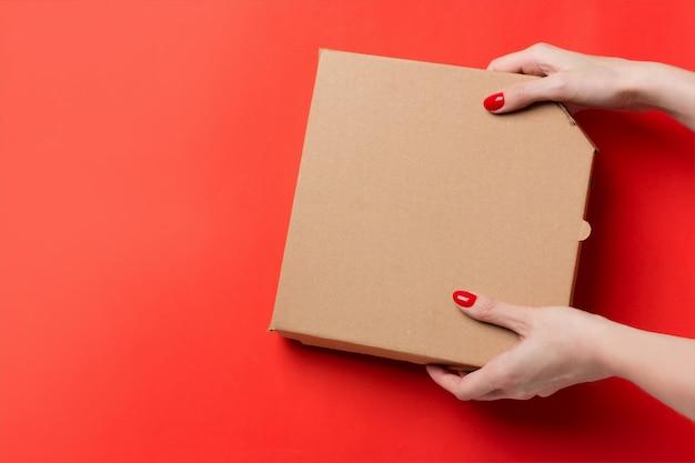 赤の背景に分離された手でピザ箱を持って宅配便