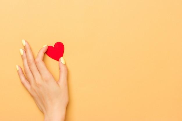 Женская рука держит красное деревянное сердце на теплом желтом фоне