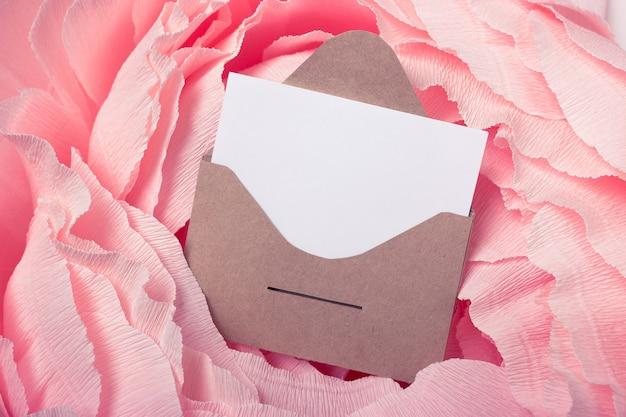ピンクの背景に添付の紙と郵便封筒をクラフトします。テキストやデザインのためのスペース。