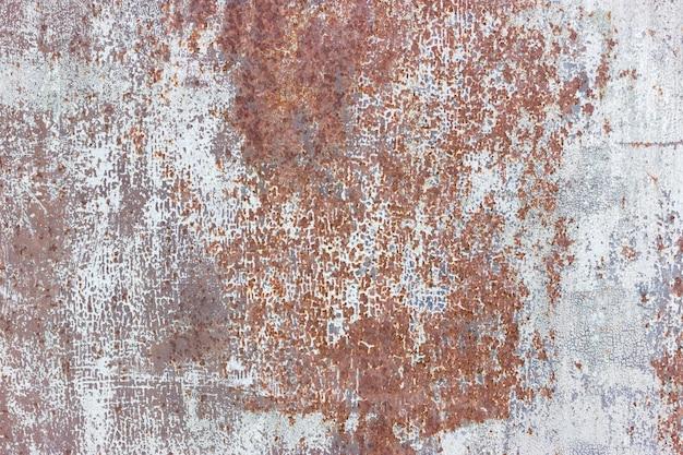 ひびの入った塗装の古い金属のテクスチャ背景。錆びた表面
