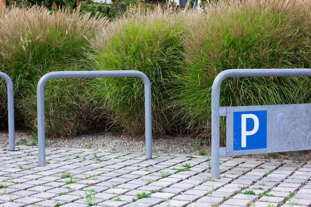 青い駐車標識と空の自転車駐車場。
